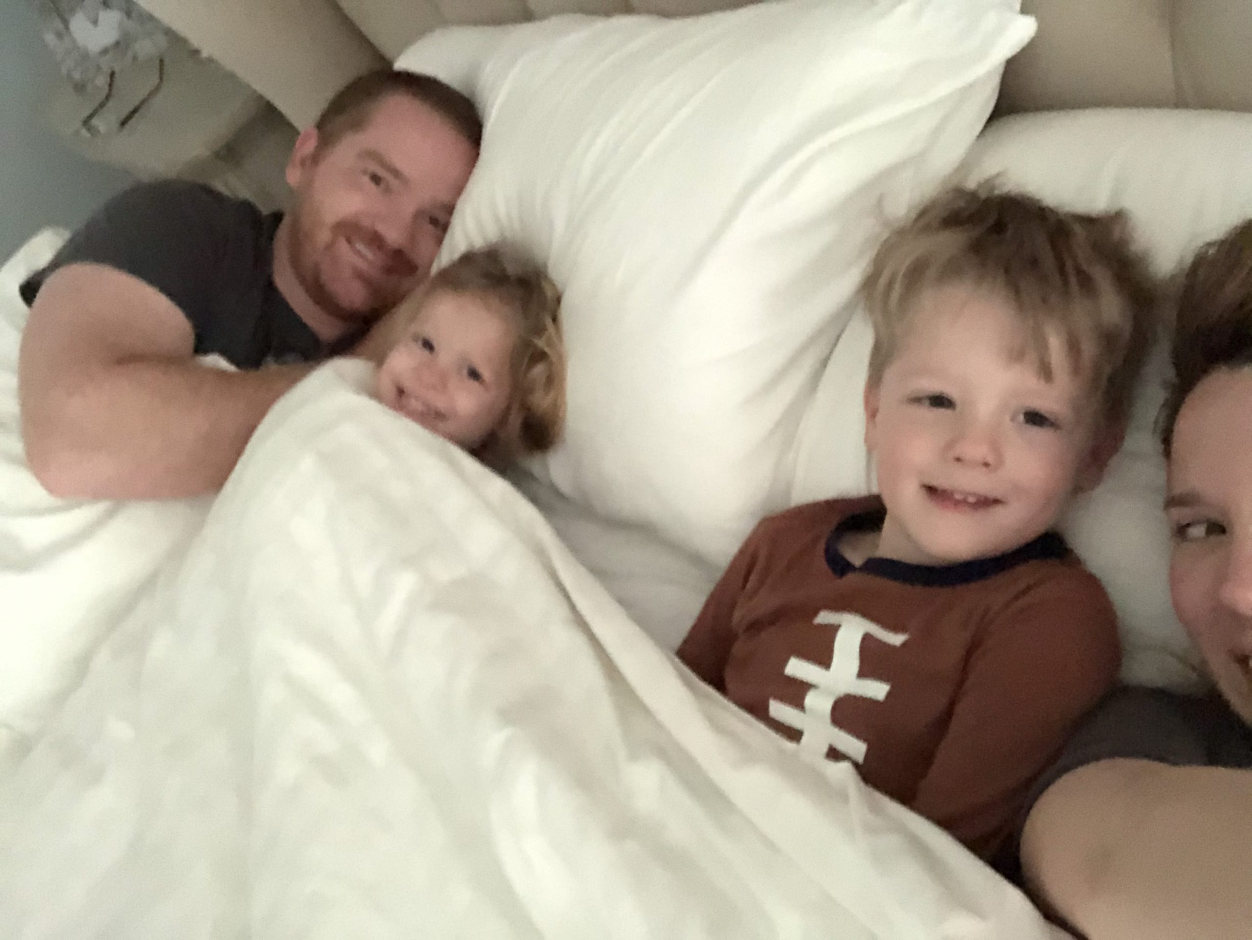 Mom, dad, and two kids laying in bed.