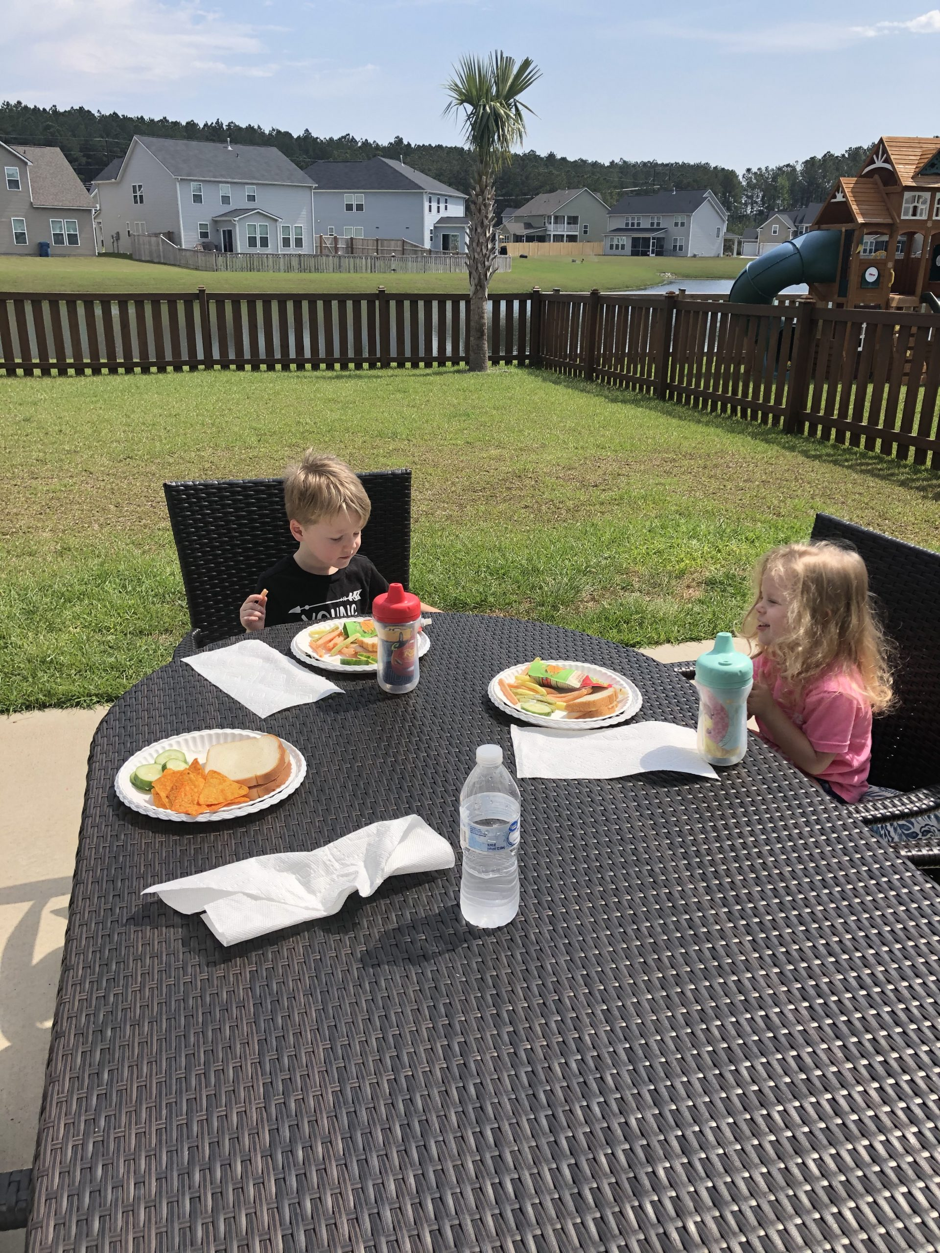 Boy and girl outside at table having lunch.