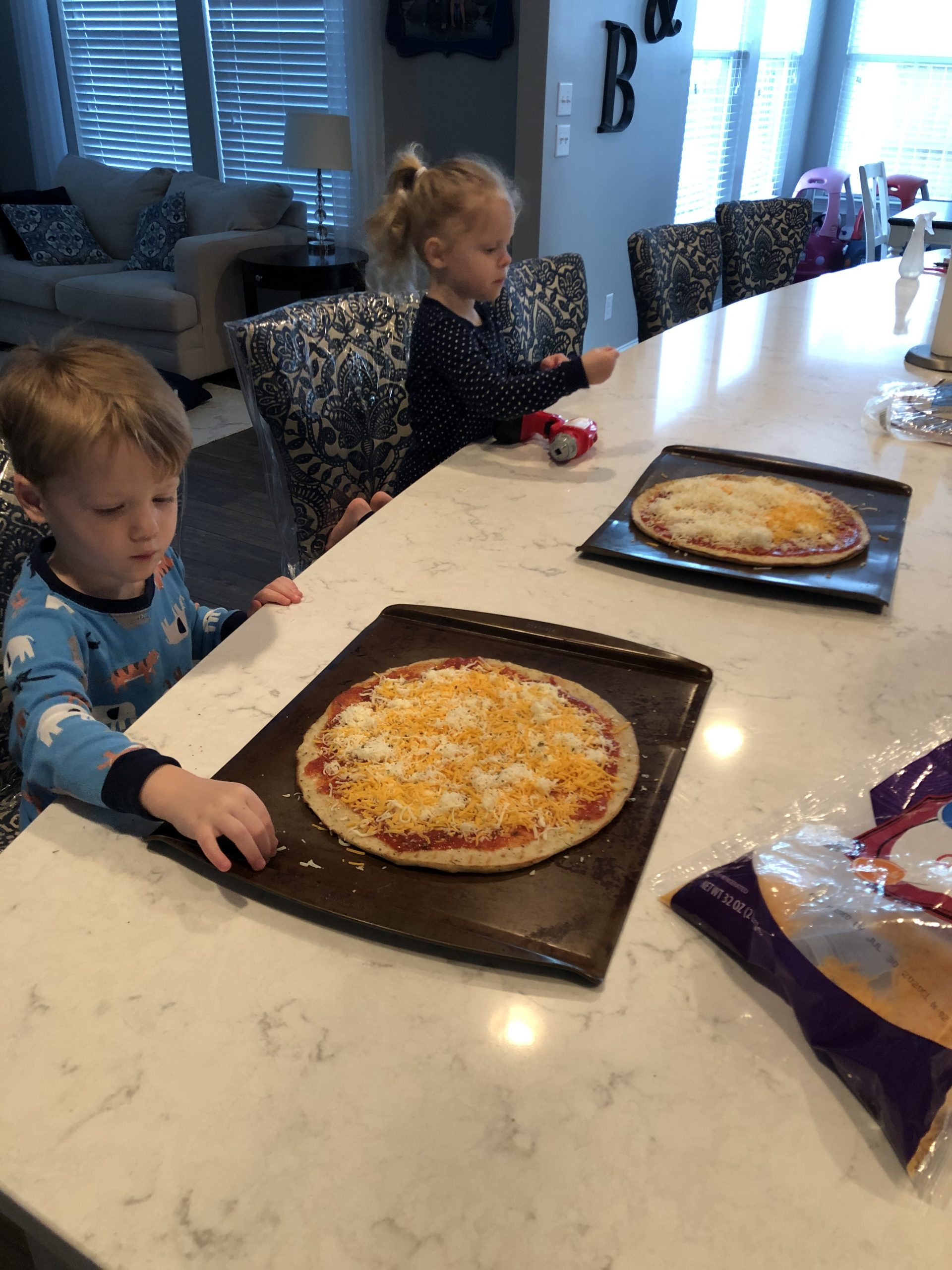 Boy and girl helping make pizzas.