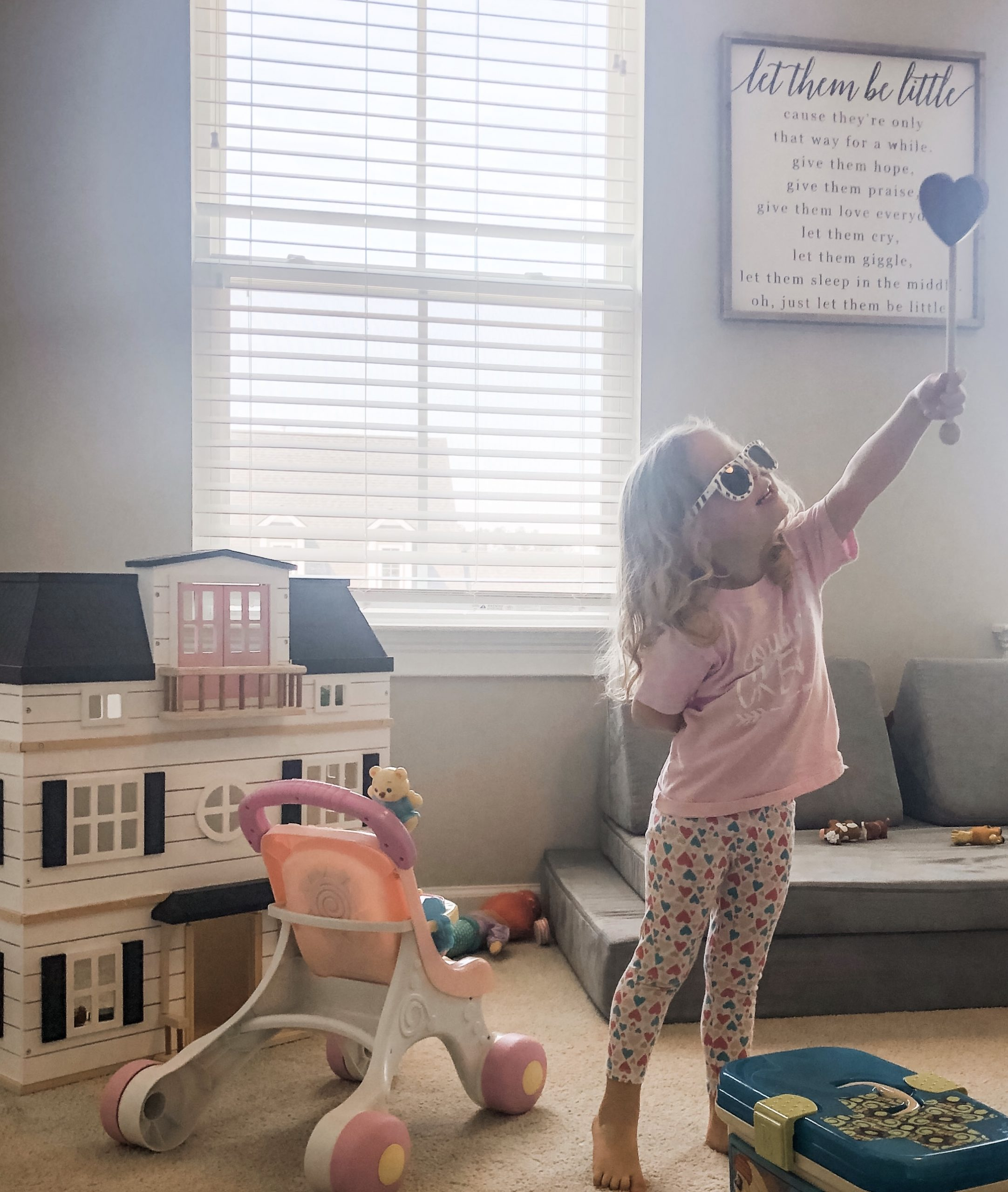 Girl with heart wand in playroom.