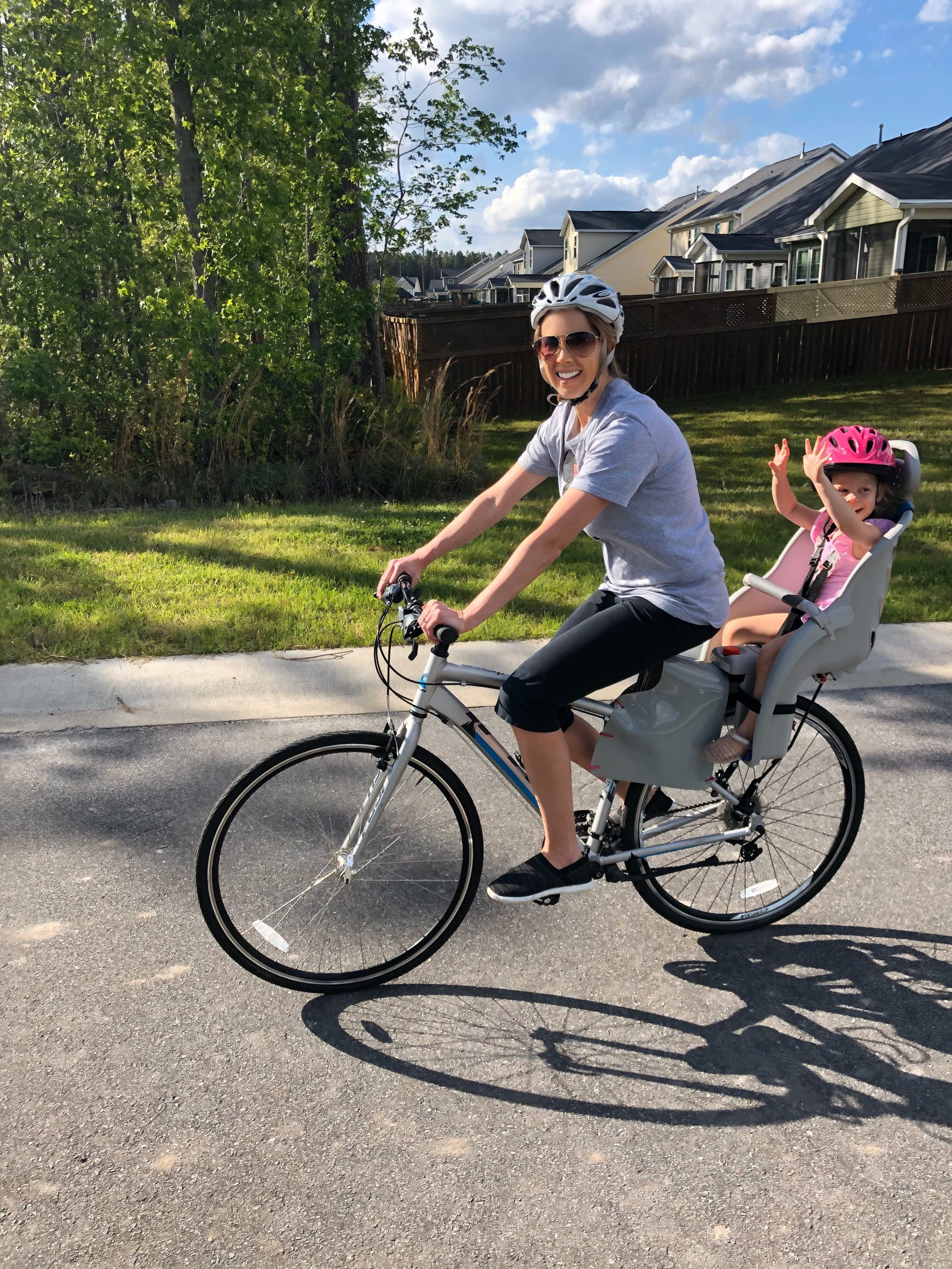 Mom on bike with daughter in bike seat.