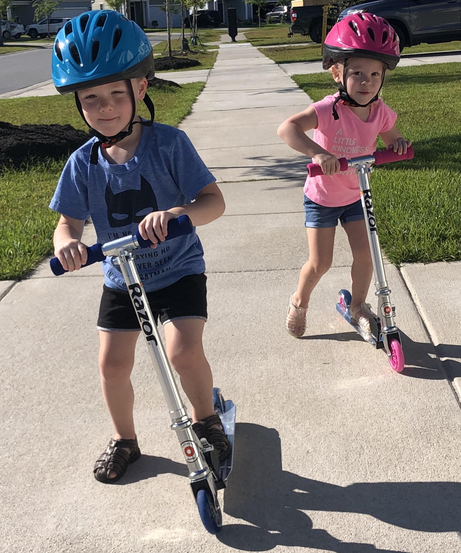 Boy and girl on scooters.