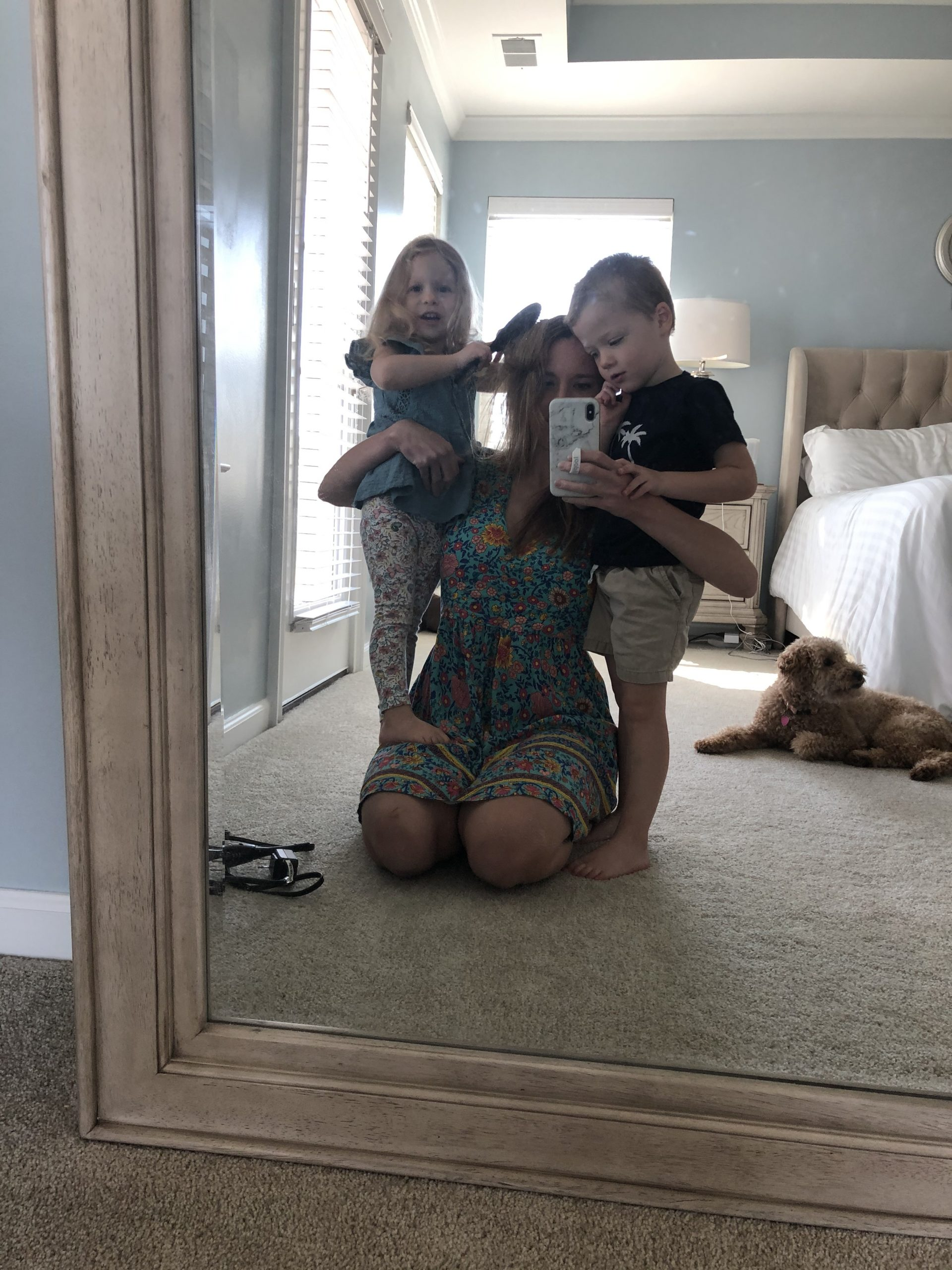 Mom with two kids in front of mirror.