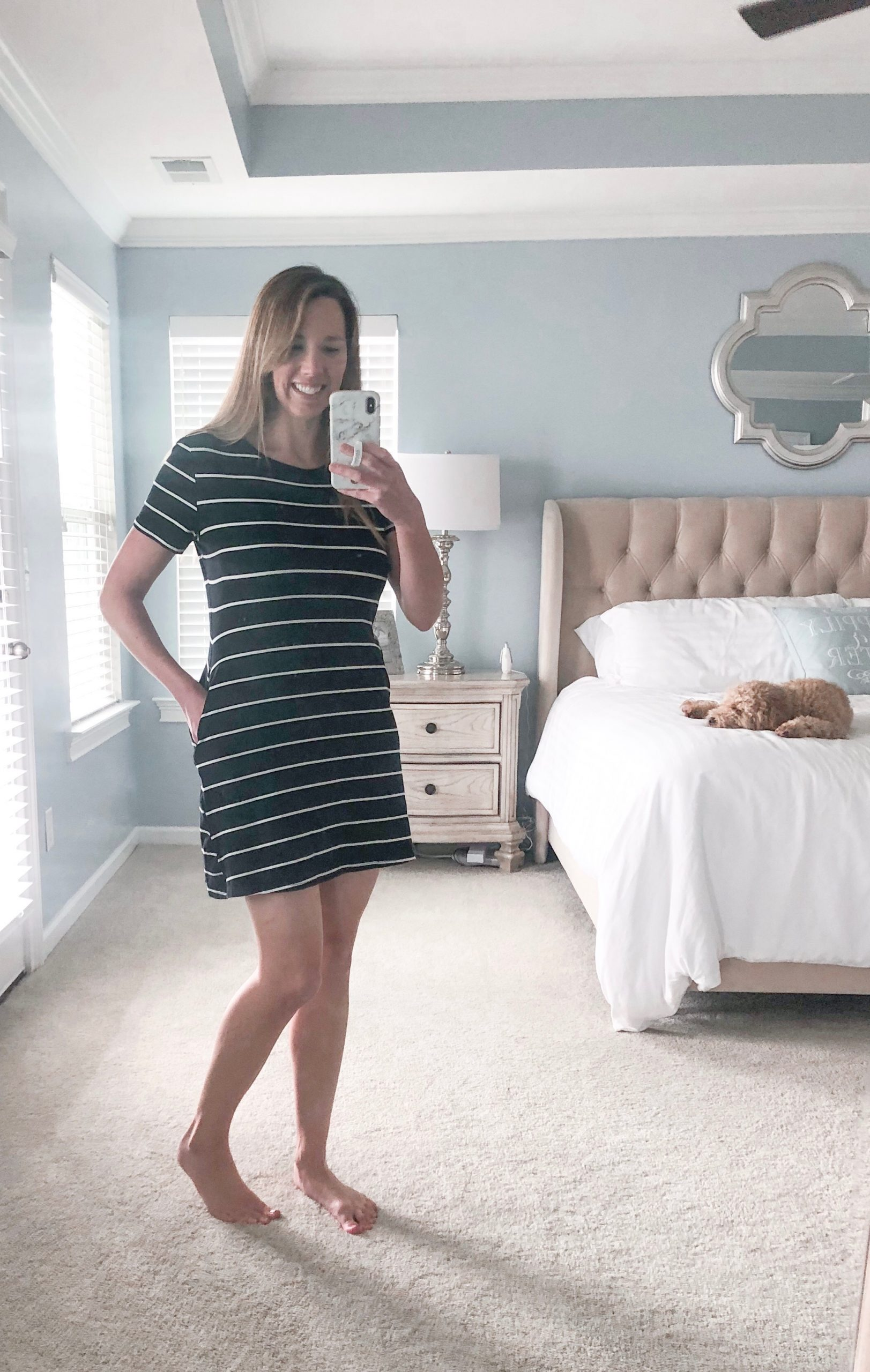 Woman wearing black and white stripped loose swing dress.