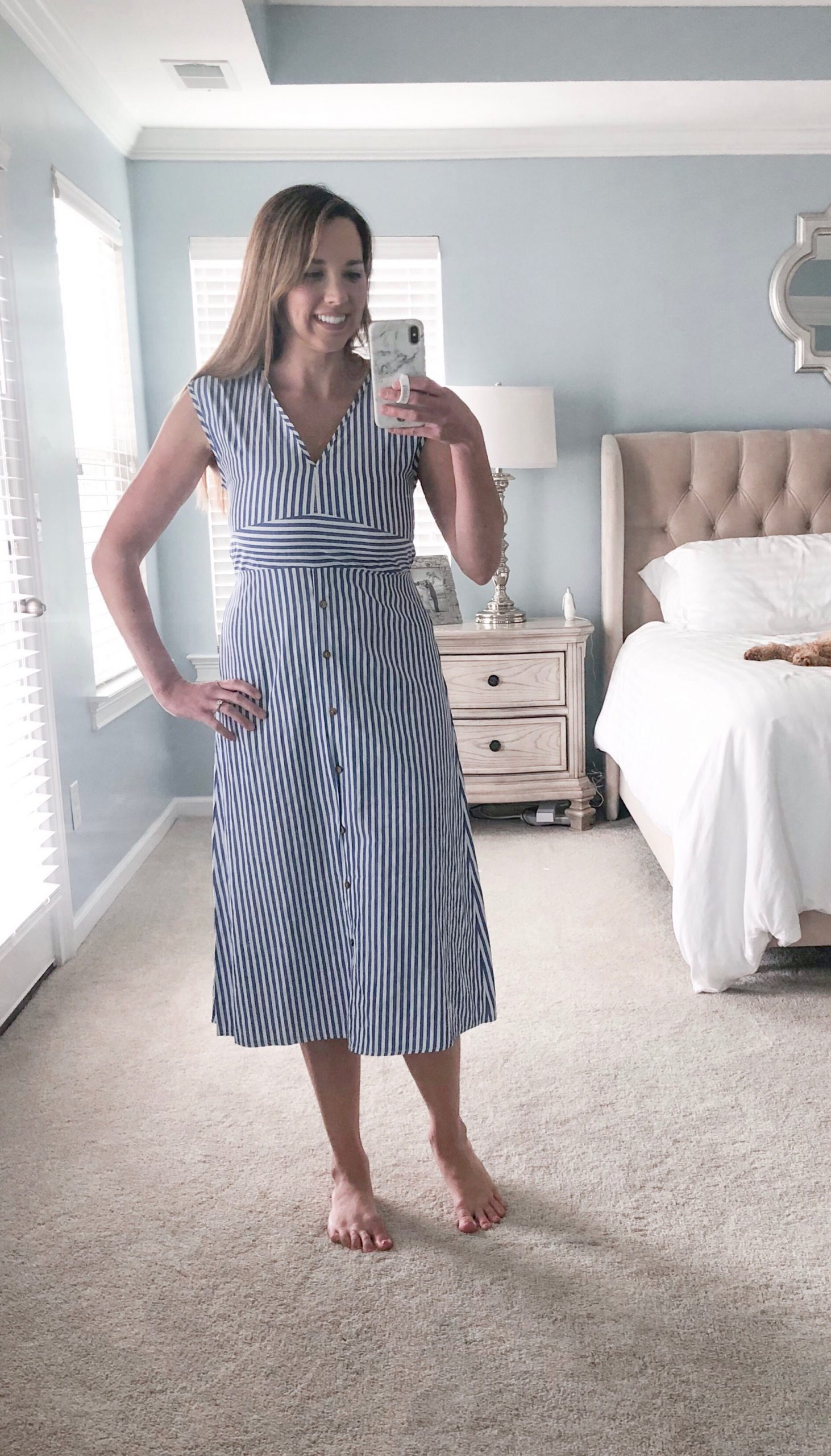 Woman wearing blue and white striped short sleeve dress.