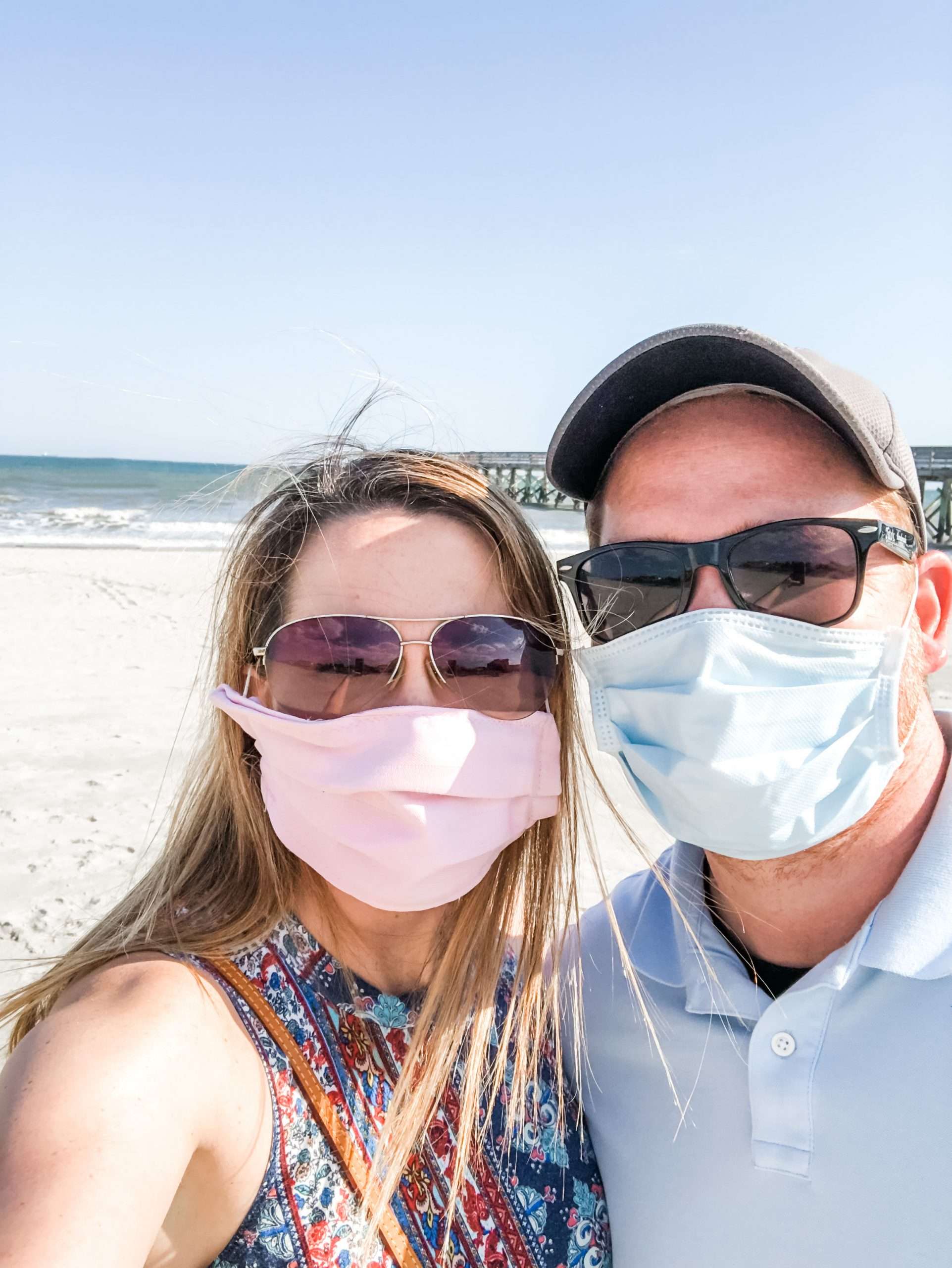 Man and woman in masks selfie in front of ocean.